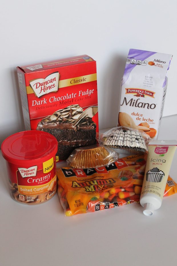 Salted caramel frosting, dark chocolate cake mix, fun cupcake liners, pumpkin candy corn, black icing, and caramel Milano cookies