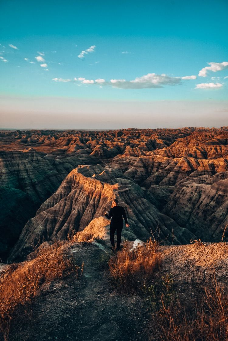 Woman walking down into Badlands at sunrise