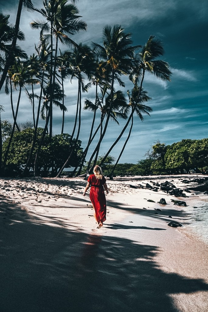 Woman in a red coverup walking along a beach on the Big Island in Hawaii