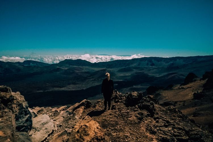 Woman standing atop the Sliding Sands trailhead before hiking into the Haleakala crater
