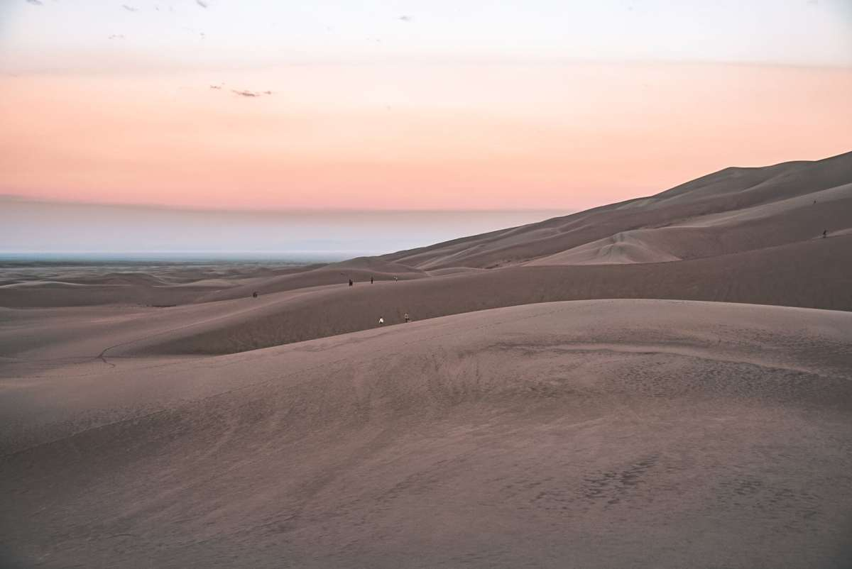 View of the sunrise from the bottom of the Great Sand Dunes. The sky is pastel.