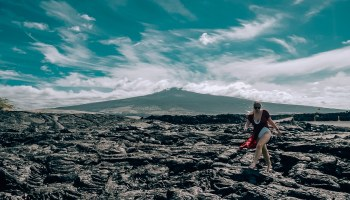 Woman in swimsuit and coverup standing on old lava rock bed with Mauna Loa in the background