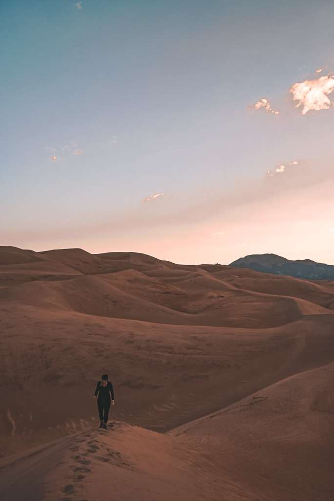 View of woman walking away onto a dune within the Great Sand Dunes during sunrise with the sky pastel pink and blue sky