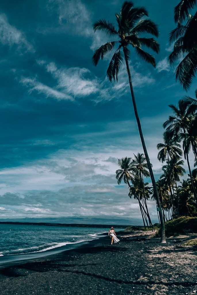 Woman walking in white swimsuit down a black sand beach with palm trees in the background and blue skies and water