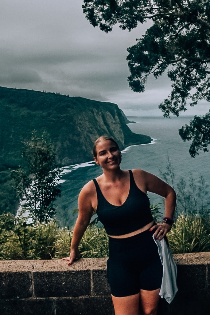Woman smiling, standing atop Waipio Valley