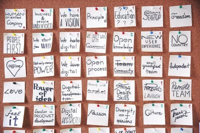 "A cork board full of pinned notes with text like ""Human-Oriented Company"" and ""We Have a Vision""."