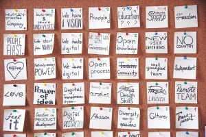 """A cork board full of pinned notes with text like """"Human-Oriented Company"""" and """"We Have a Vision""""."""