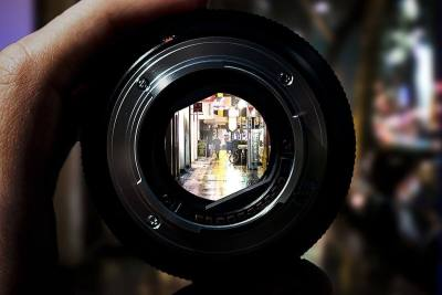 A camera lens focused on a street view, with everything around the lens blurry.