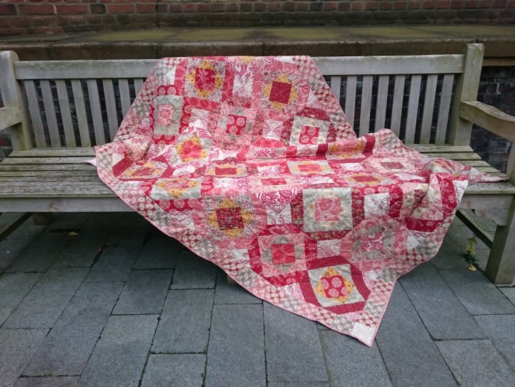 'Terrazzo' - a single quilt in colours of red, pink, cream yellow and stone in a pattern reminiscent of Italian mosaic floors, designed and made by Amanda Jane Textiles