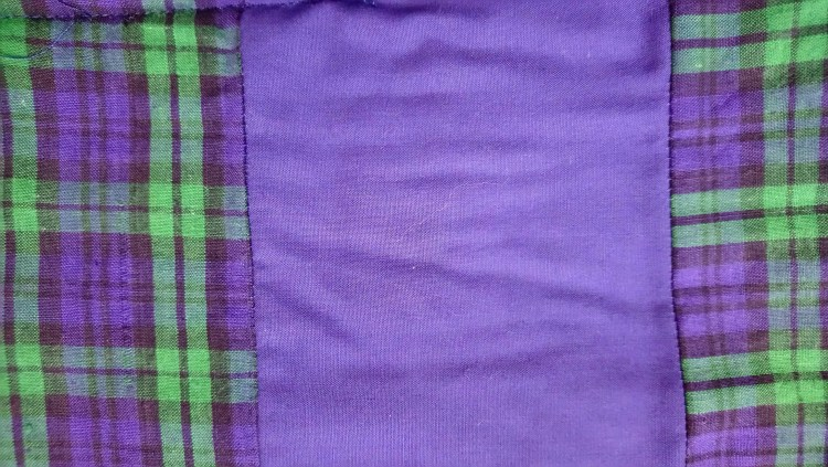 Photo showing how to insert a strip into a quilt back to make it wider
