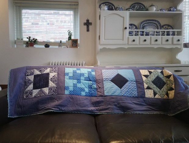 A quilt entitled 'Make a Quilt in 2019' on the back of a sofa