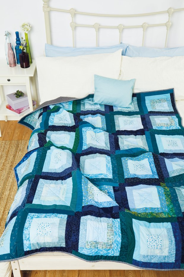A blue and green quilt using a modern version of log cabin blocks