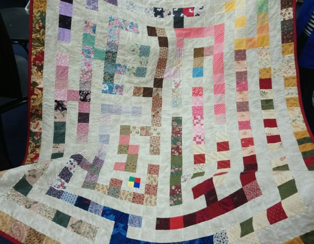 a quilt with a white background and multi-colured squares which form a maze