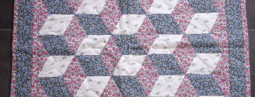 small quilt made with 'baby blocks' design in pink blue and white