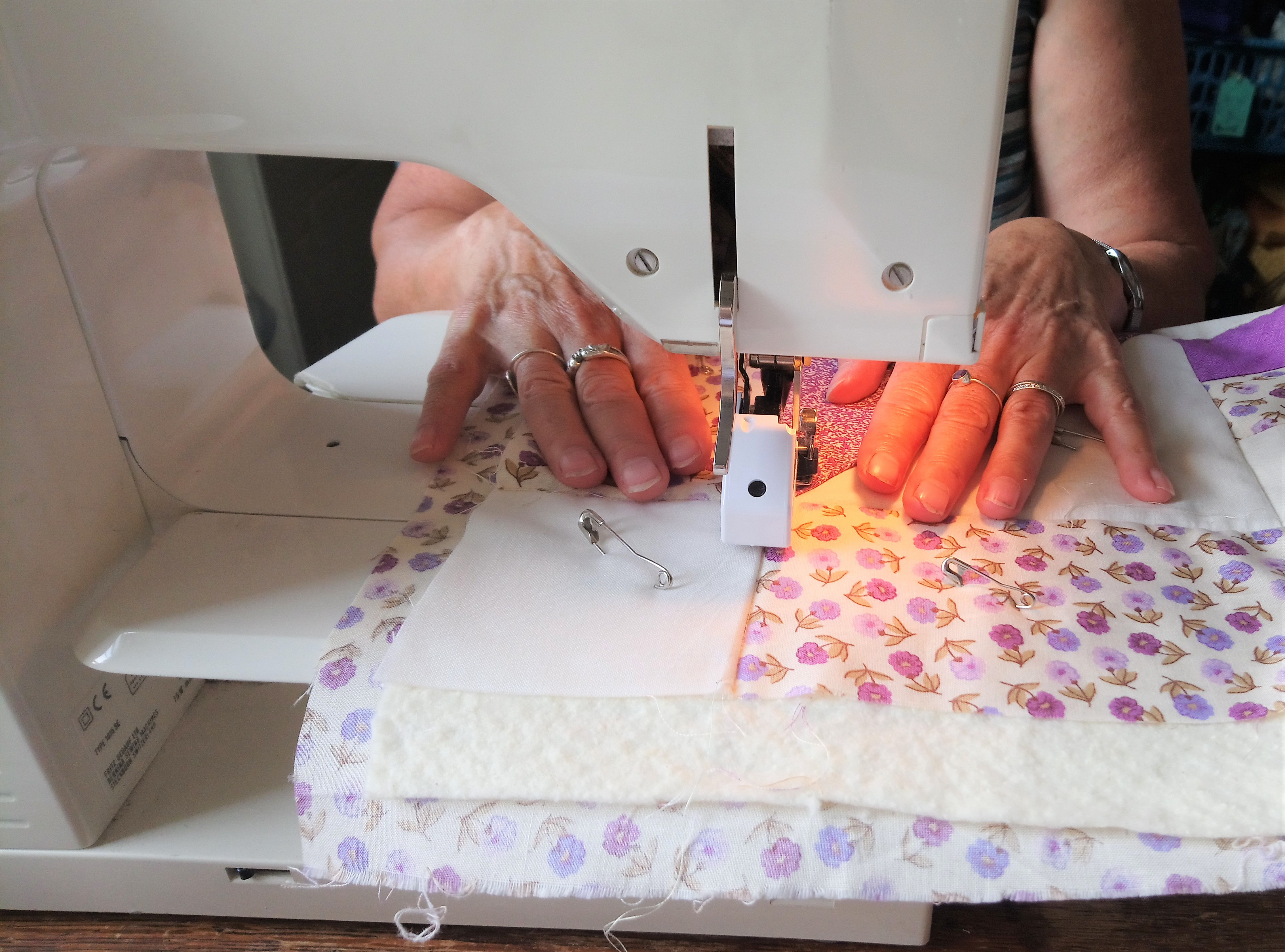 a woman making a quilt, sewing it on a machine, illustrating the 'Quilt in a Day' class taught by Amanda Jane Ogden