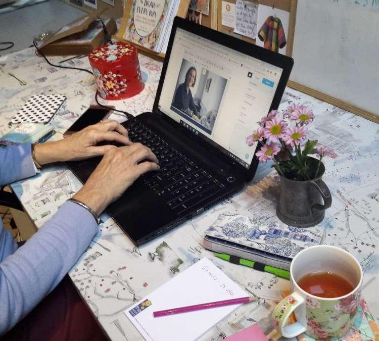 A person writing a blog post at a desk with lap-top, diary, notepad, notebooks and mobile, with hands on the keyboard. There is a mug of tea and flowers on the table