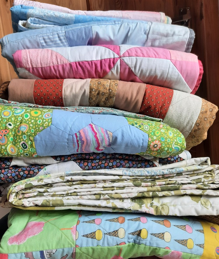 A pile of quilts on a chair, all made by Amanda Jane Ogden