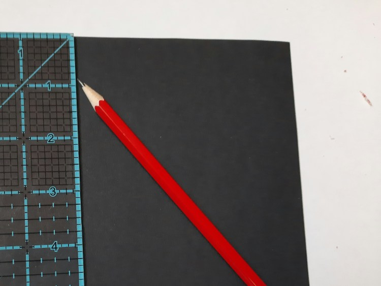 marking the cardboard with a ruler and pencil