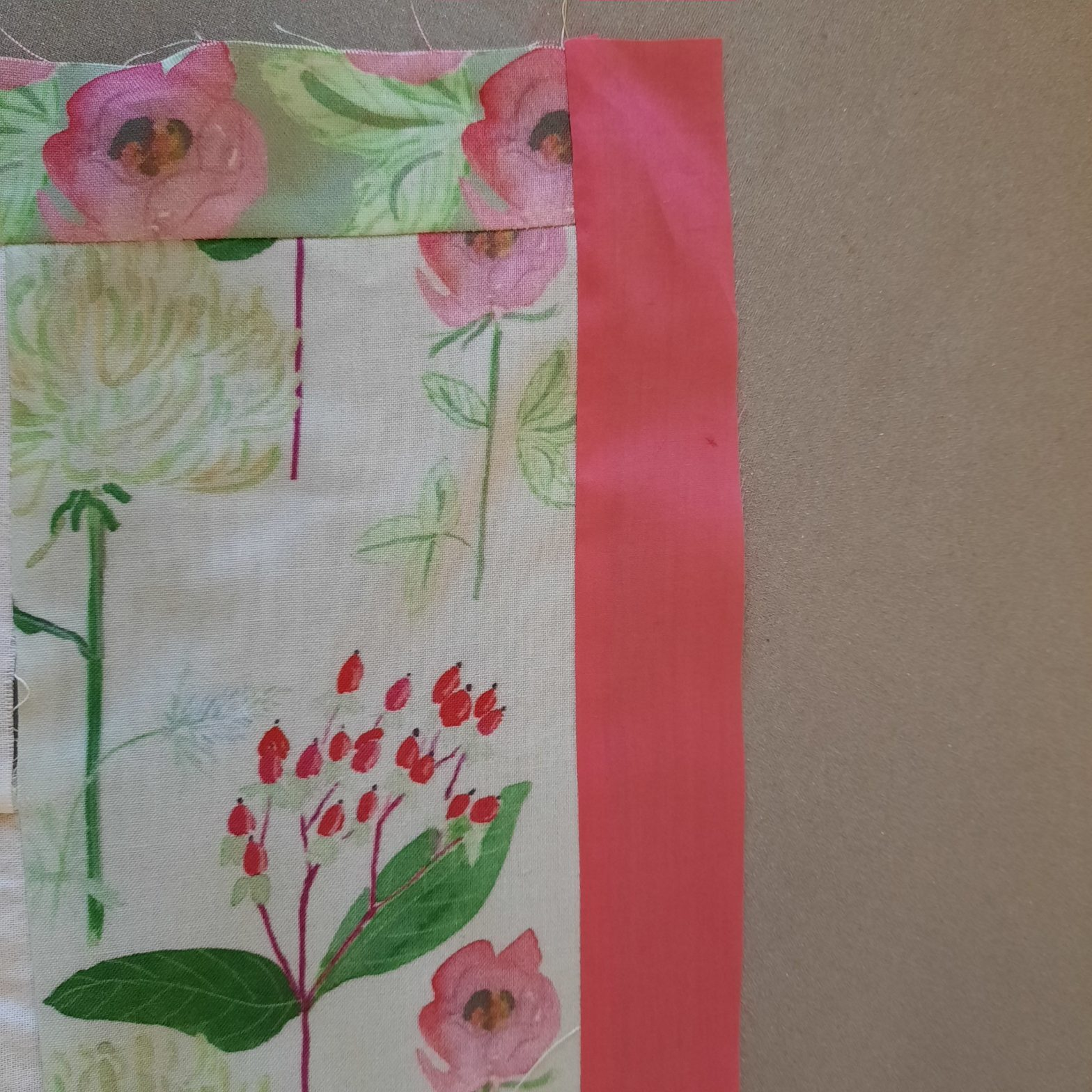Adding the pink internal border to the 'Summer Bouquets' quilt, the photo shows the narrow roses border at the top and the pink border at the right of the quilt-top
