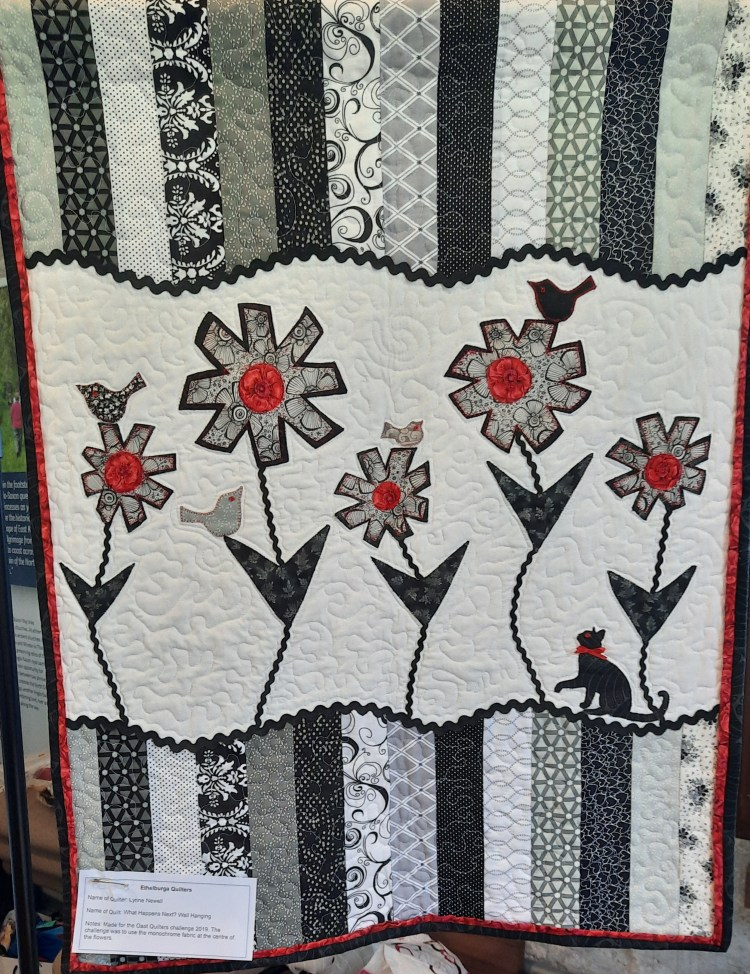 Black and white quilt with touches of red, depicting flowers leaves, a bird and a cat set against a background of stripes: 'What happens next?' wall-hanging by Lynne Newell