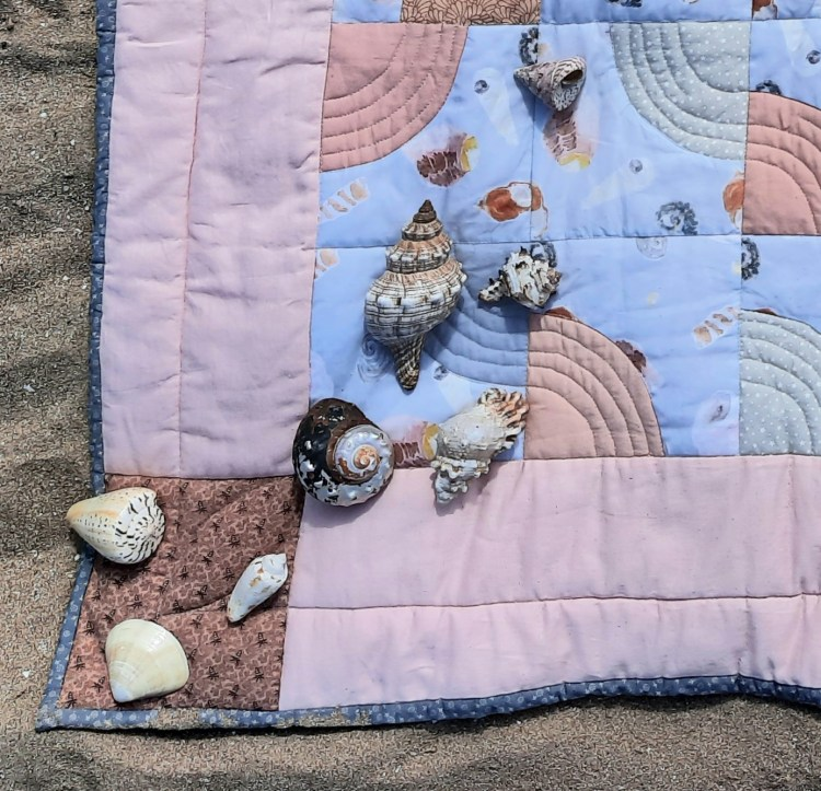She Sells Sea Shells quilt (detail), showing the corner of the quilt with the shells that inspired the background fabric of the quilt