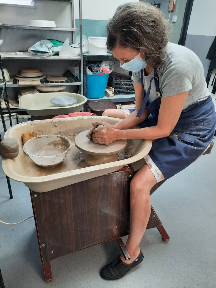 learning a new craft - centering the clay on a potter's wheel