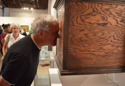 A visitor peers into a box at the Thermal PHX 2014 show at MonOrchid Gallery.