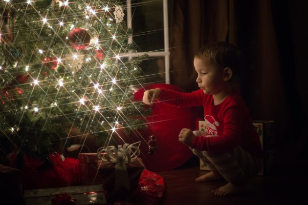 little boy wearing red christmas pajamas holding santa ornament next to christmas tress