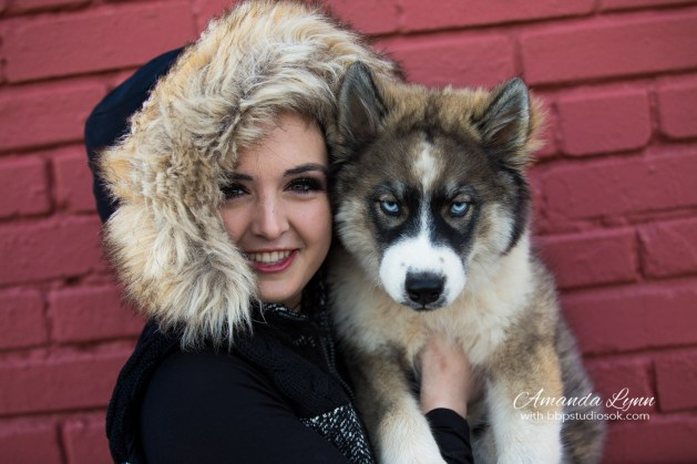 high school senior girl wearing winter coat holding puppy standing in front of red brick wall in oklahoma city