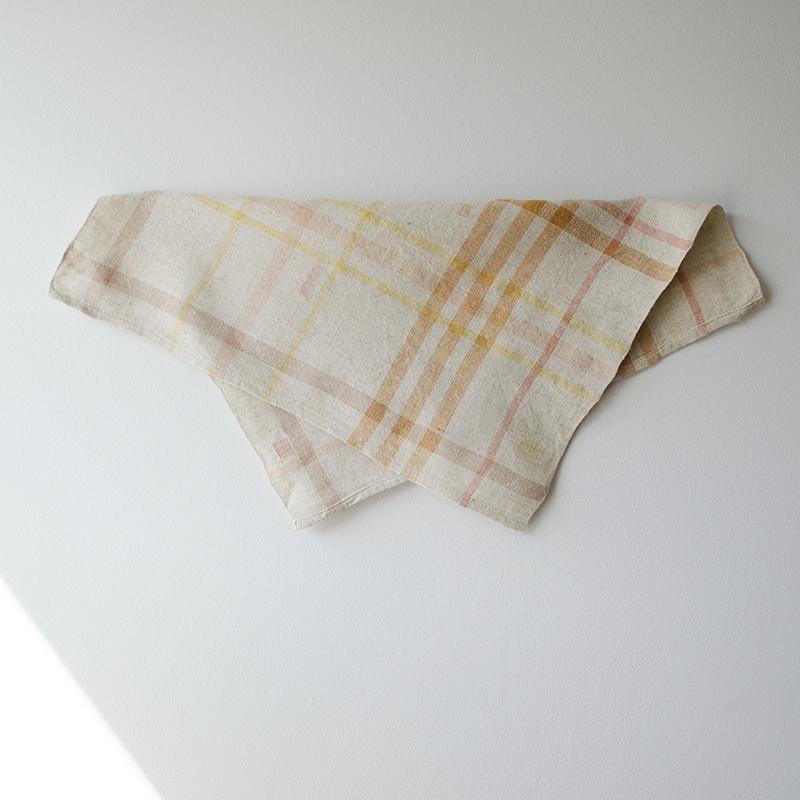 Folded naturally dyed napkin in random stripes