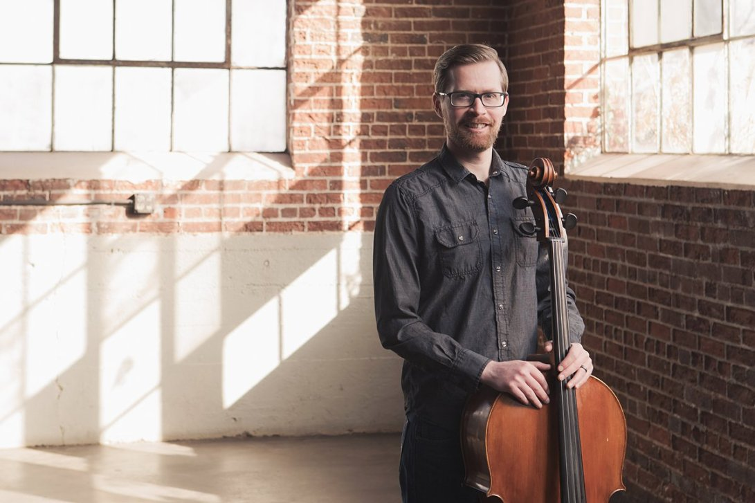 man smiling with cello