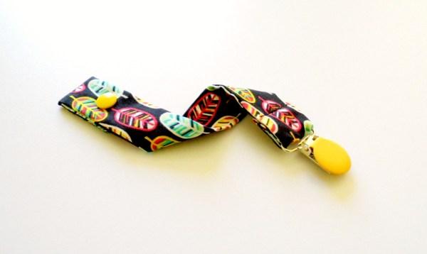 attache-tetine-noire-plumes-jaune-accroche-sucette-accessoire-bebe