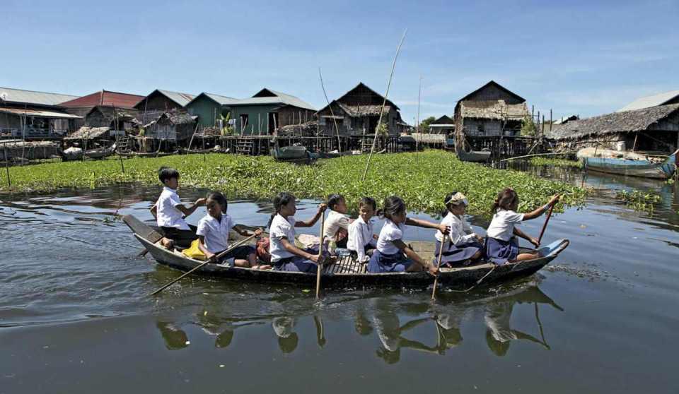 Crianças a deslocarem-se para a escola numa aldeia flutuante do Tonle Sap
