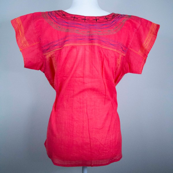 Traditional handmade Mexican embroidered red blouse on a mannequin
