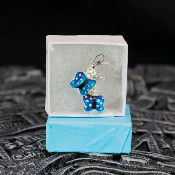 Handblown blue butterfly glass earrings displayed in an open blue box, Aztec calendar in the foreground, dark background