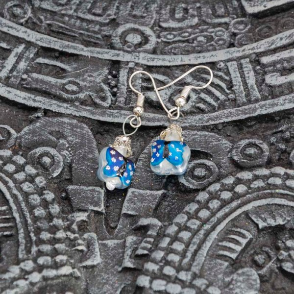 Handblown blue butterfly glass earrings displayed on top of an Aztec calendar