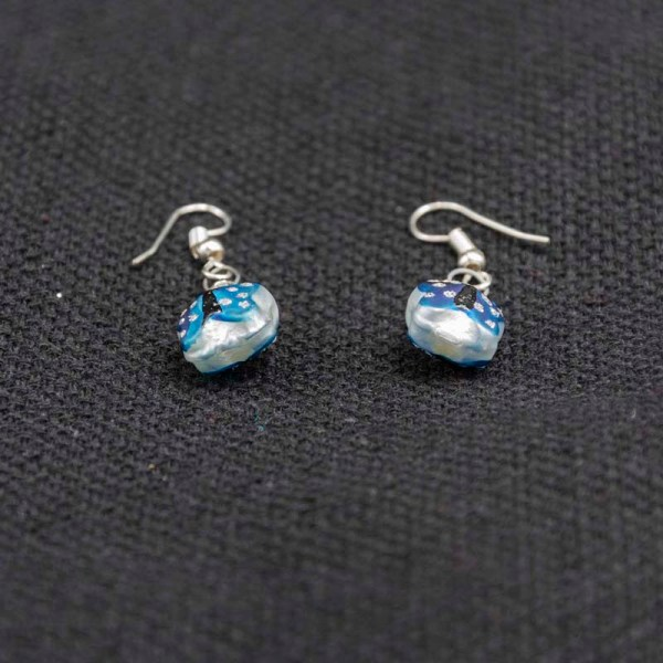 Handblown blue butterfly glass earrings on a gray fabric.