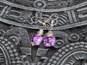 Handblown purple butterfly glass earrings displayed on top of an Aztec calendar