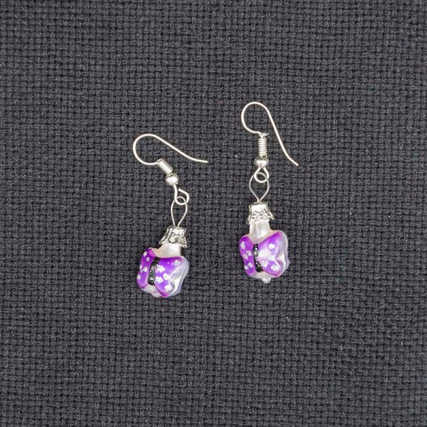 Handblown purple butterfly glass earrings on a gray fabric.