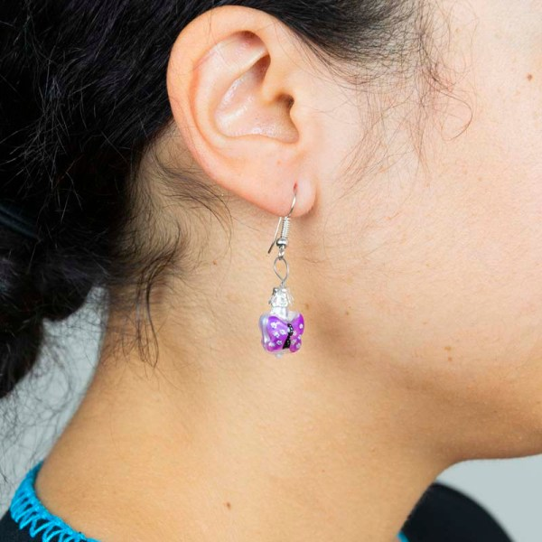 Woman wearing Handblown purple butterfly glass earrings