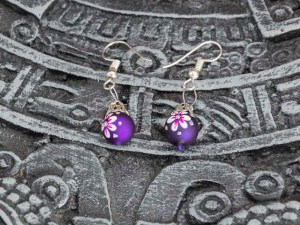 Cute little hand-blown glass purple earrings with white flowers on a Aztec calendar