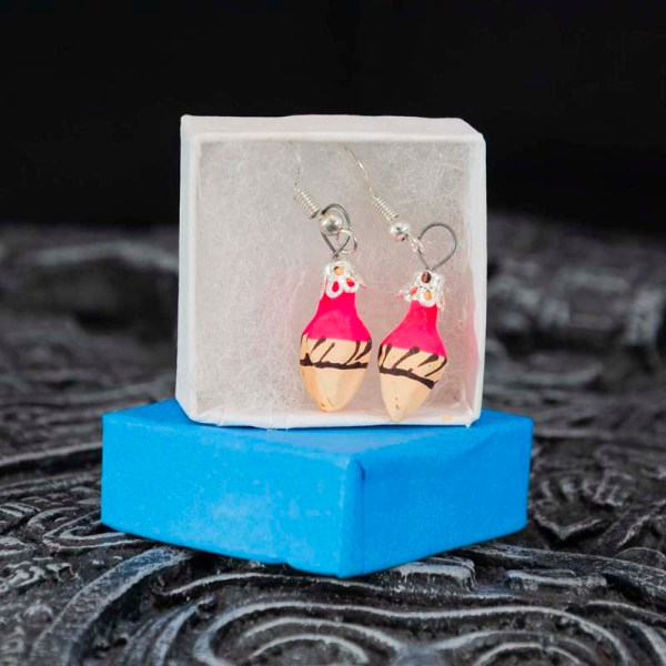 Cute handblown glass pink ice cream cone earrings in a box on a Aztec calendar