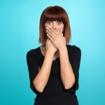 beautiful, young woman, with a surprised face expression, covering her mouth, on blue background