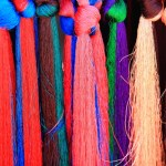 Set of manycolored threads for weaving hanging on the outside of a shop in a street market in the 3840 ms.high Shigatse city-county and prefecture in the Yarlung Tsangpo and Nyang Chu rivers junction. Tibet-China.