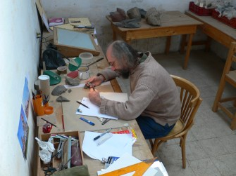 Most artefacts are drawn by a specialist illustrator: here, Andy Boyce produces pencil drawings of fragments of hard-stone sculpture.
