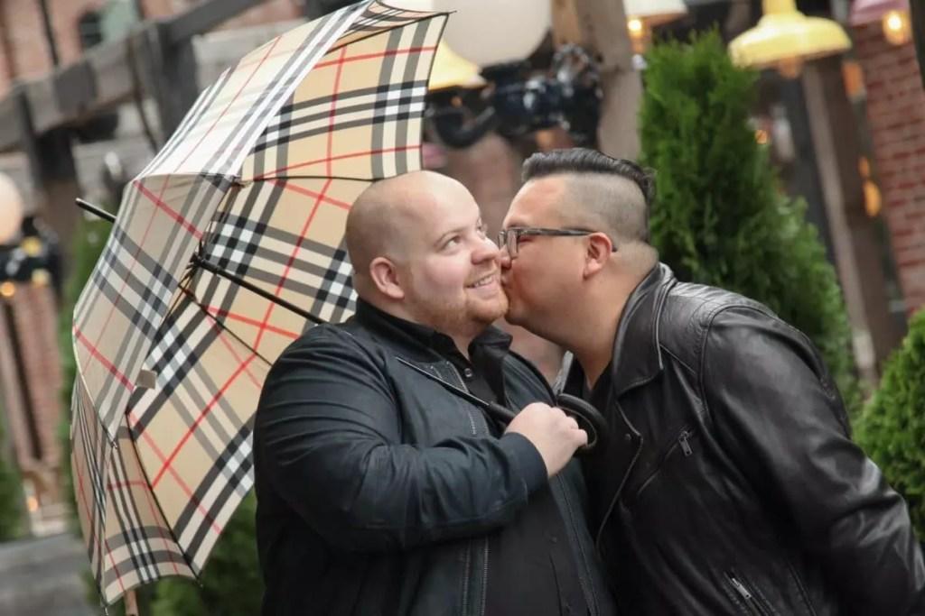 Mark kissing Pedro cheek under an umbrella