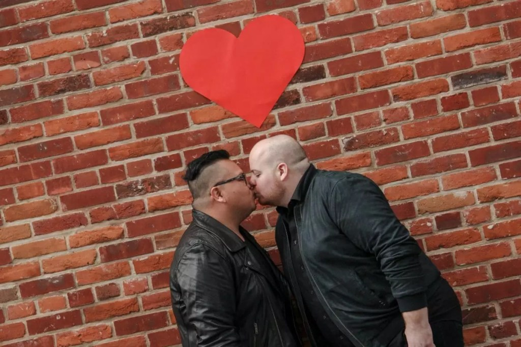 Mark and Pedro kissing under a red heart