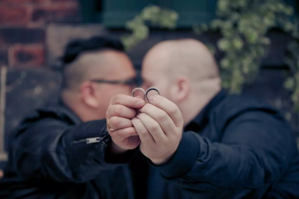 Mark and Pedro holding up their engagement rings