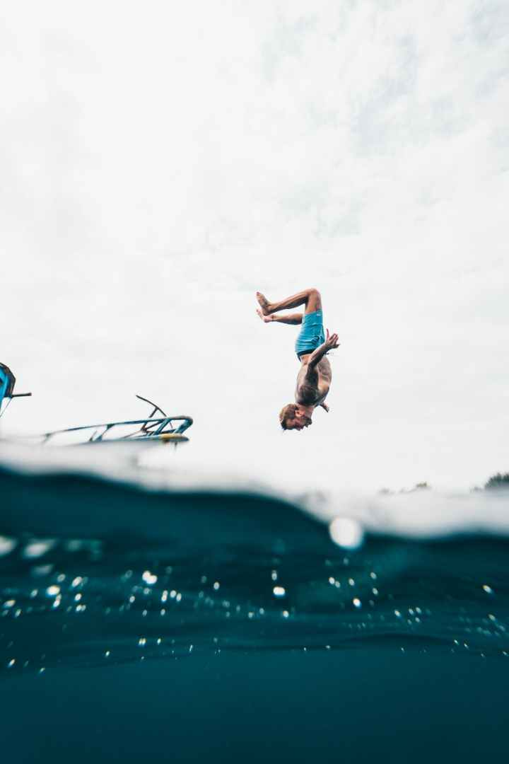 man wearing blue shorts about to dive on body of water- the zest for life is one of the fundamentals of true happiness.