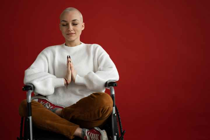 mindful woman meditating with closed eyes in wheelchair- mindfulness is essential to happiness.